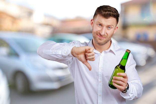 El hombre muestra que la cerveza es mala