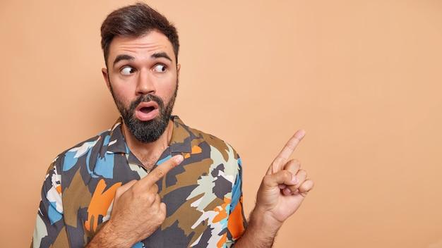El hombre muestra una revelación inesperada indica en la promoción muestra el espacio de la copia viste una camisa colorida aislada en beige