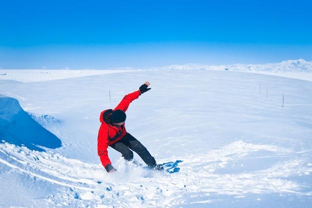 El hombre se mueve en snowboard