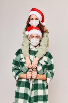 Hombre y mujer abraza divertidas máscaras médicas navideñas