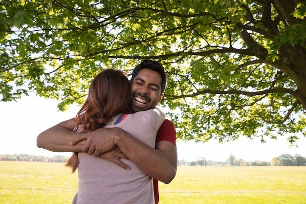 Hombre y mujer abrazándose antes de hacer yoga al aire libre