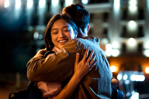 Hombre y mujer abrazándose por la noche en las luces de la ciudad