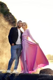 Hombre y una mujer abrazándose en el verano al atardecer en ropa hermosa. pareja de enamorados se encuentra en la orilla de las rocas bajo el sol, abrazándose y besándose en las salpicaduras de agua