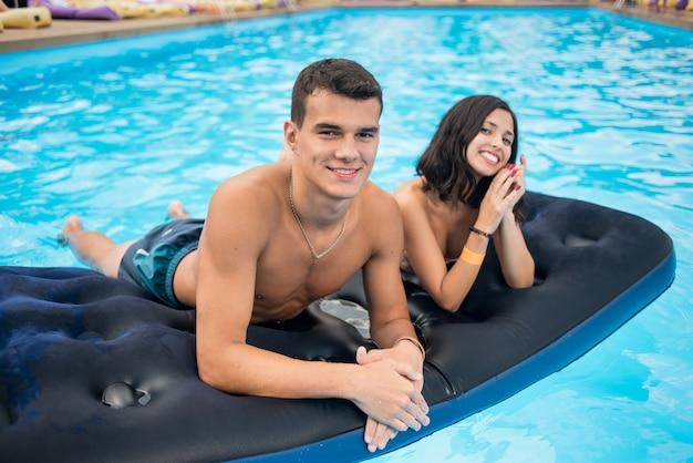 Hombre con mujer acostada en un colchón en la piscina