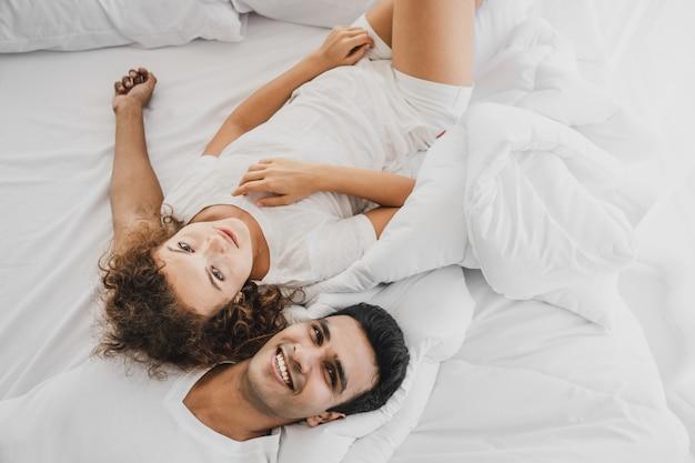 Un hombre y una mujer acostados en una cama.