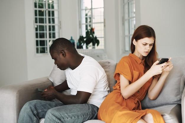 Hombre y mujer africana sentada con smartphone