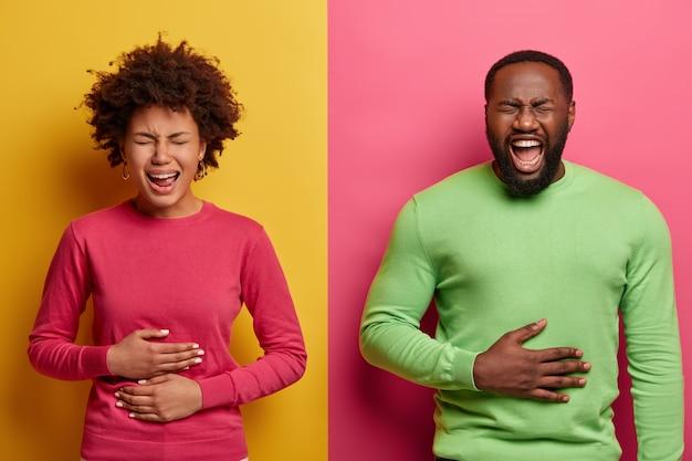 Hombre y mujer alegre hilarante tocan los estómagos de la risa