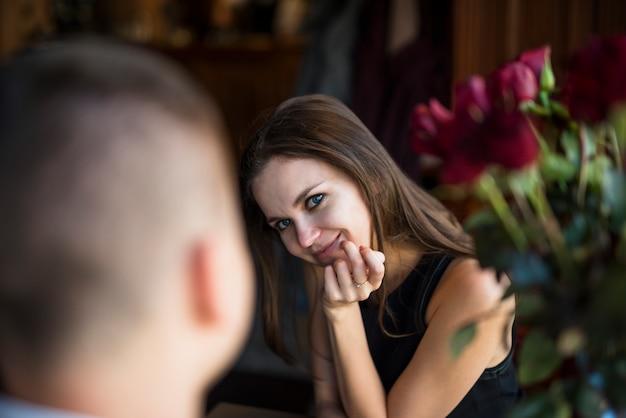 Hombre y mujer alegre joven con la mano en la barbilla cerca de las flores