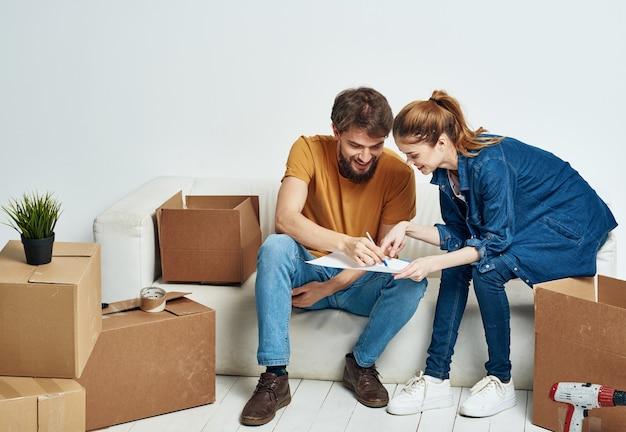 Hombre y mujer alegre en el sofá en casa interior cajas de mudanza