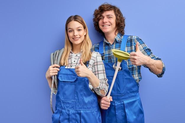 Hombre y mujer alegres fontaneros en uniforme azul con herramienta de émbolo