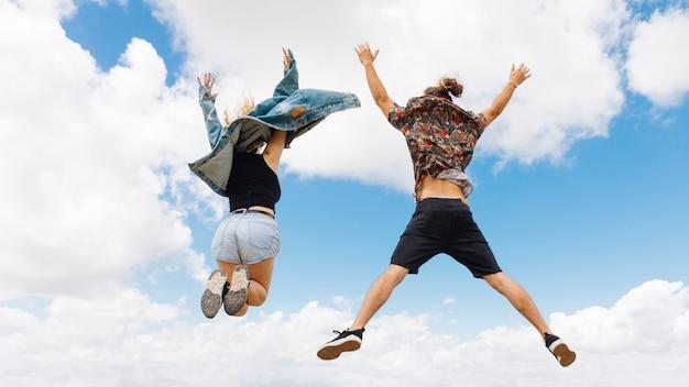 Hombre y mujer aptos saltan de alegría