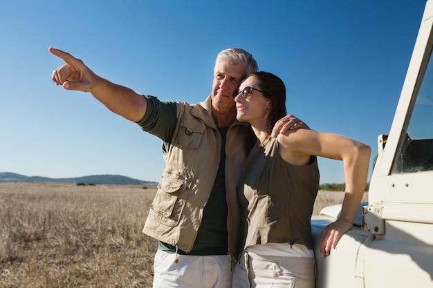 Hombre con mujer apuntando por vehículo en campo