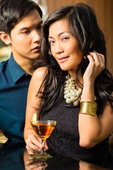 Hombre y mujer en asia en el bar con cócteles