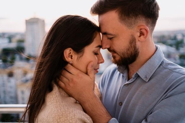 Hombre y mujer en el balcón al atardecer en la ciudad