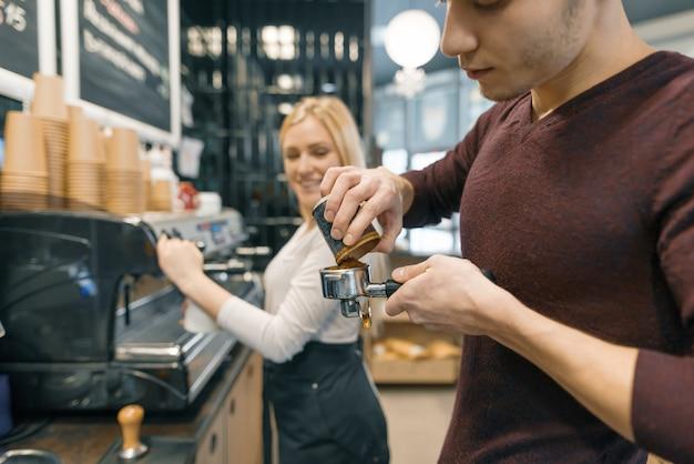 Hombre y mujer del barista que hacen el café, par de los jóvenes que trabajan en cafetería.