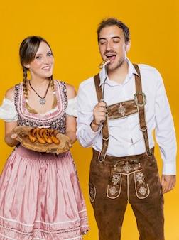 Hombre y mujer bávara intentando salchichas