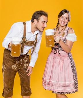Hombre y mujer bávaros con jarras de cerveza