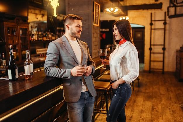 Hombre y mujer bebe vino tinto en barra de bar