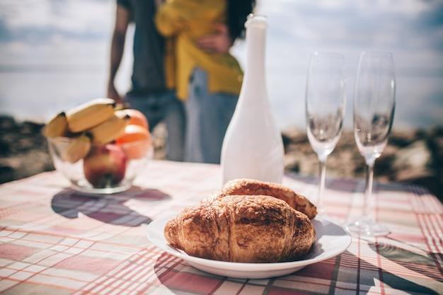 Hombre y mujer beben champán cerca del agua en una mesa portátil plegable viajes, turismo - picnic cerca del agua. pareja de aventuras. concepto de viaje en coche.