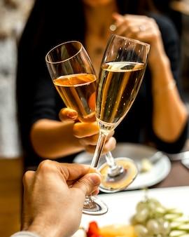 Hombre y mujer beben champaña con un plato de frutas