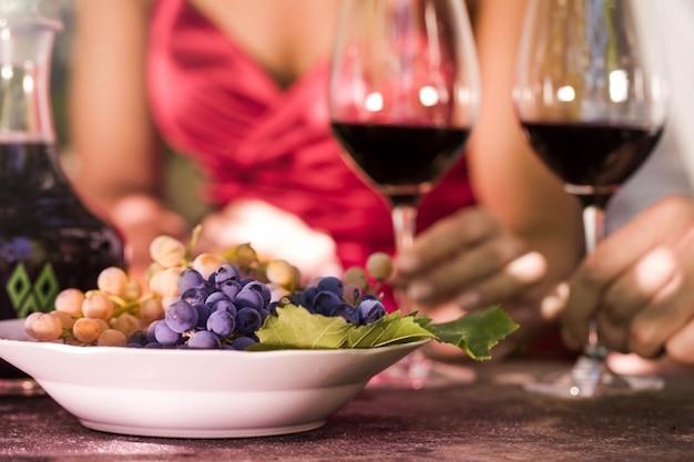 Hombre y mujer bebiendo leen vino y comen uvas