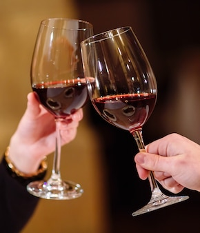 Hombre y mujer bebiendo vino tinto. en la imagen, manos de primer plano con gafas.