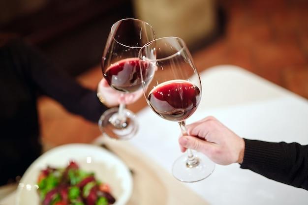 Hombre y mujer bebiendo vino tinto.