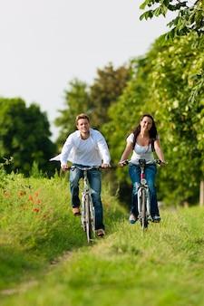 Hombre y mujer en bicicleta por un camino soleado
