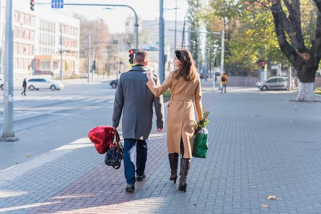 Hombre y mujer con bolsas de calle.