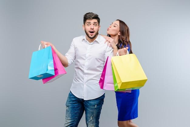 Hombre y mujer con bolsas de compras que obtuvieron en venta