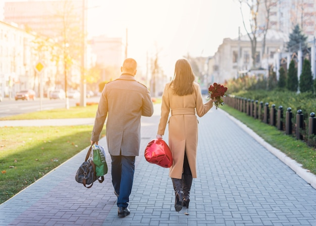 Hombre y mujer con bolsas y flores en calle.