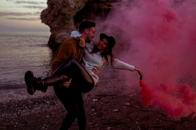 Hombre con mujer en brazos con bomba de humo rosa
