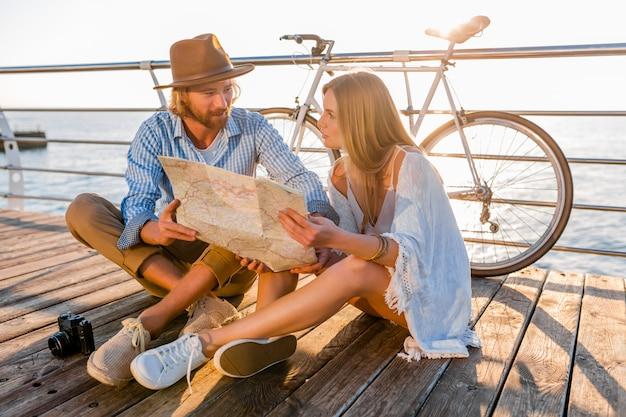 Hombre y mujer con cabello rubio estilo boho hipster moda divirtiéndose juntos, mirando en el mapa turismo