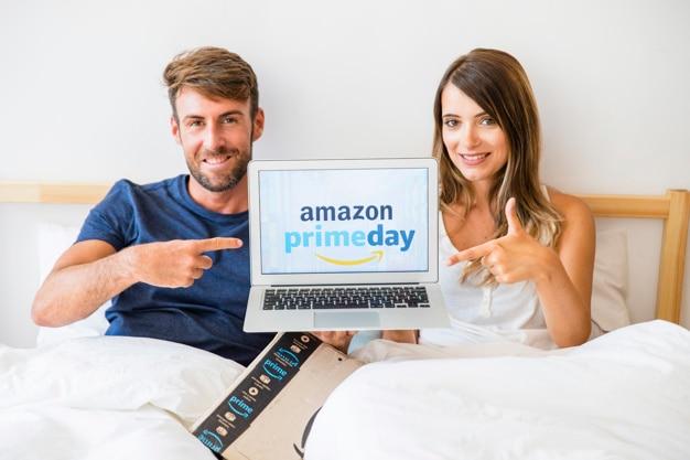 Hombre y mujer en la cama con las manos que muestran al portátil