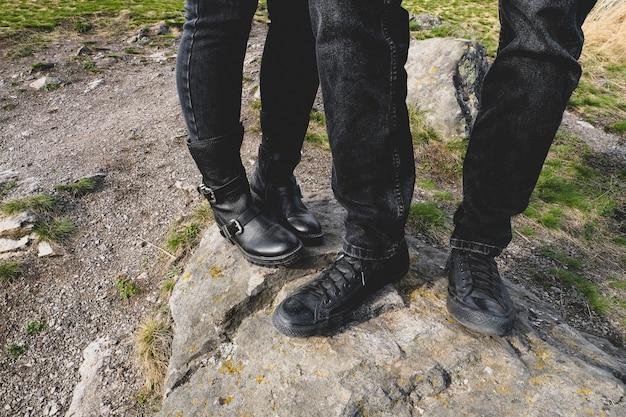 Hombre y mujer caminando en las montañas, de pie sobre una piedra, primer plano de las piernas
