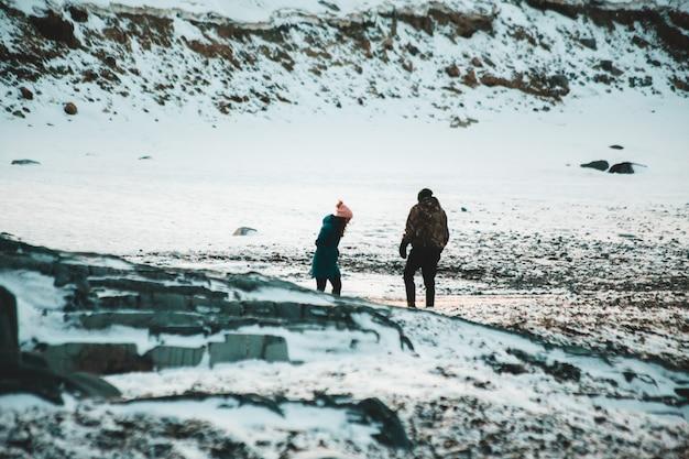 Hombre y mujer caminando sobre terreno cubierto de nieve durante el día