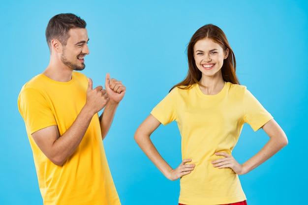 Un hombre y una mujer en camisetas de colores brillantes posando juntos, una pareja