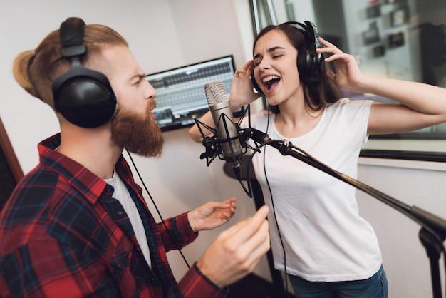 Un hombre y una mujer cantan una canción en un estudio de grabación moderno.