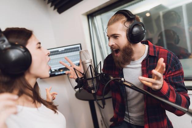 Un hombre y una mujer cantan una canción en un moderno estudio de grabación.