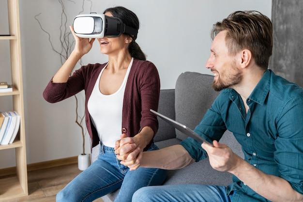 Hombre y mujer en casa con casco de realidad virtual y tableta