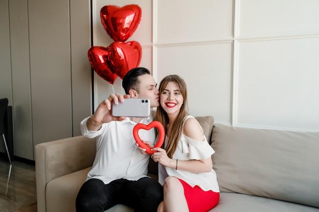 Hombre y mujer en casa haciendo selfie con corazón y globos en el teléfono