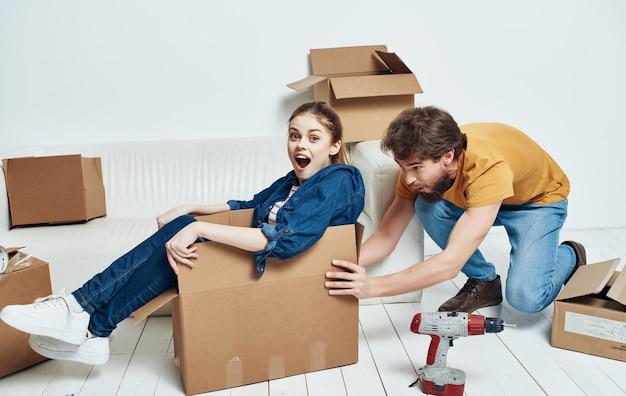 El hombre y la mujer en casa en el sofá blanco moviendo cajas de inauguración
