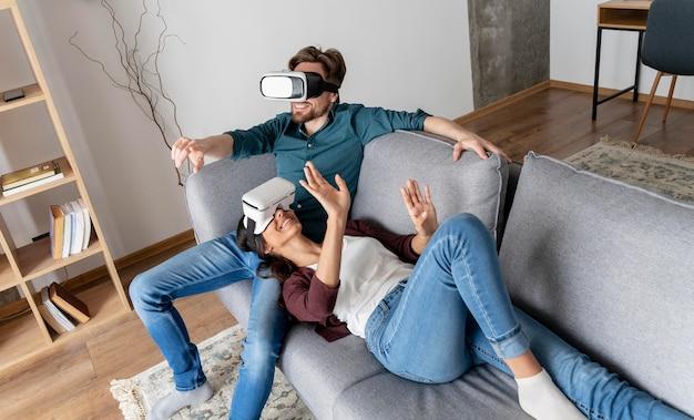 Hombre y mujer en casa en el sofá con casco de realidad virtual