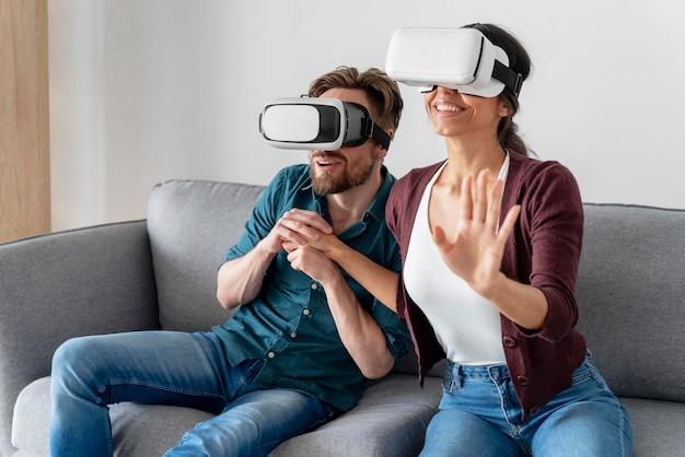 Hombre y mujer en casa en el sofá divirtiéndose con casco de realidad virtual