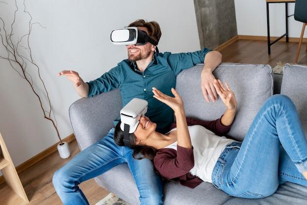 Hombre y mujer en casa en el sofá explorando casco de realidad virtual