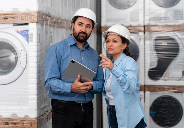 Hombre y mujer con casco trabajando en almacén