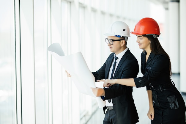 El hombre y la mujer con cascos sostienen el plan del proyecto en el edificio. negocio de la construcción.