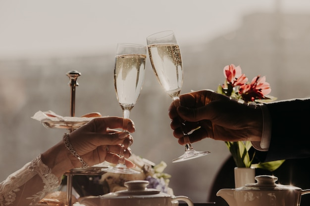 Hombre y mujer celebran boda tintineo vasos con champán