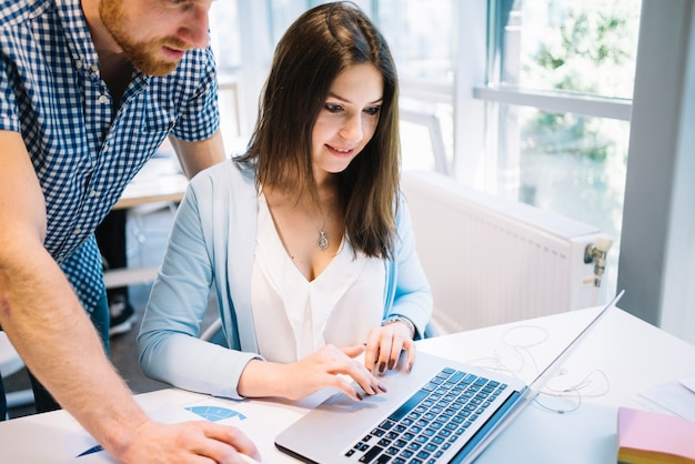 Hombre y mujer colaborando en la computadora portátil