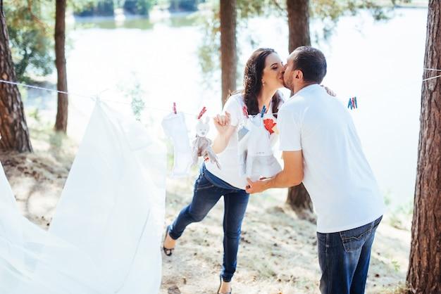 Hombre y mujer colgando ropa bebé en la cuerda al aire libre